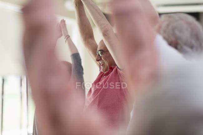Lächelnd aktiven senior Mann streckte die Arme über Kopf in Übung — Stockfoto