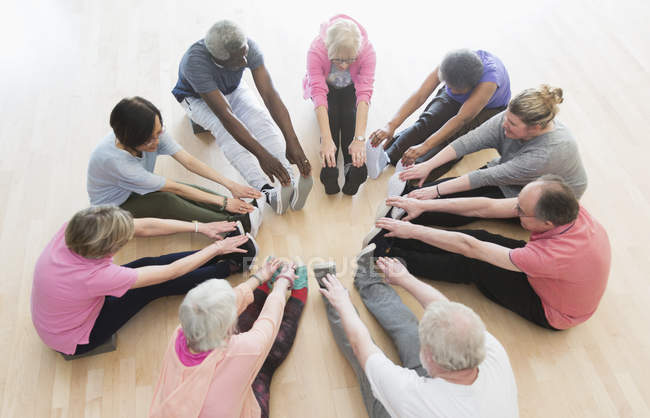 Active seniors stretching legs in circle in exercise class — Stock Photo