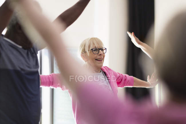 Smiling active senior woman stretching arms in exercise class — Stock Photo