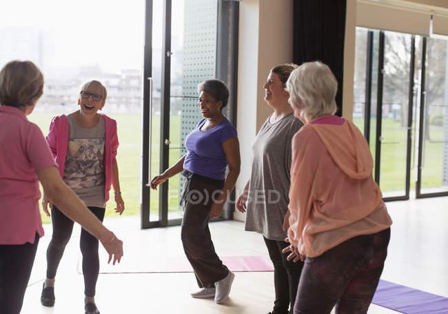 Smiling active senior women talking in exercise class — Stock Photo