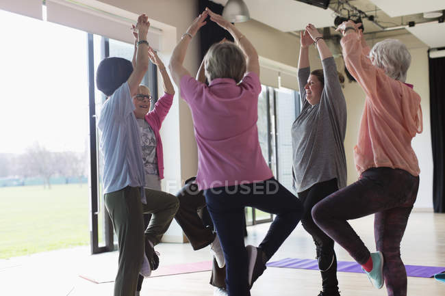 Active senior women exercising, practicing yoga tree pose — Stock Photo