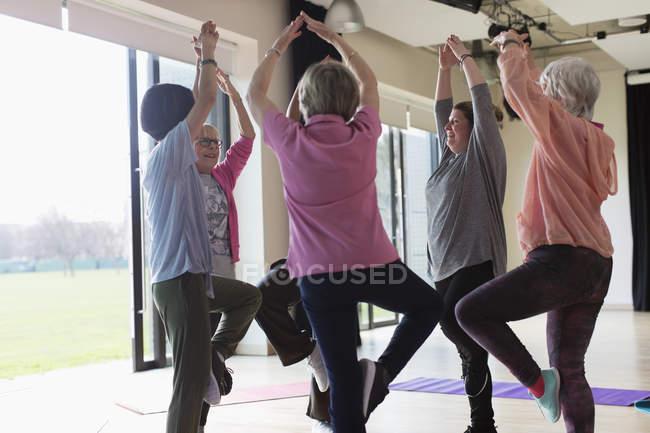 Активні старші жінки здійснюють, практикуючи йога поза дерева — стокове фото
