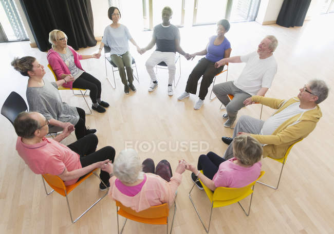 Active seniors holding hands in circle, meditating in community center — Stock Photo