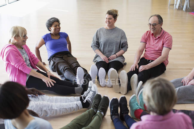 Instructor and active seniors stretching legs in circle in exercise class — Stock Photo