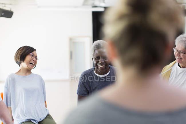 Смеющиеся активные пенсионеры, разговаривающие в общественном центре — стоковое фото
