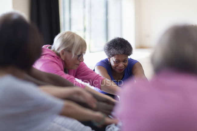 Active seniors stretching in exercise class — Stock Photo