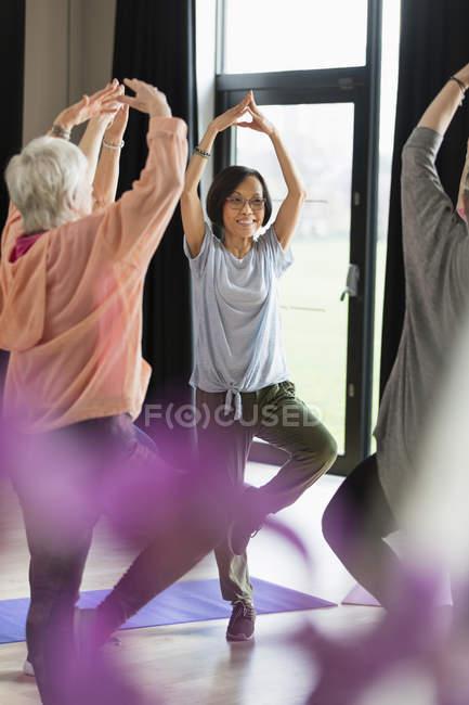 Усміхнене активних старшим жінка фізичних вправ, практикуючи йога поза дерева — стокове фото