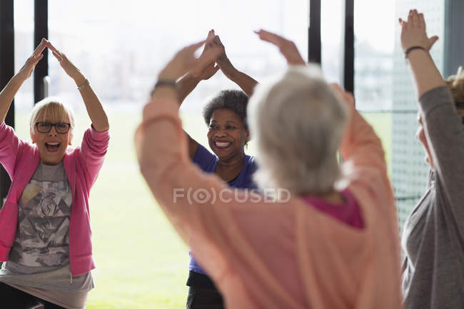 Happy active senior women exercising, stretching arms overhead in exercise class — Stock Photo