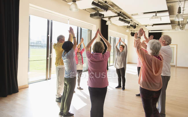 Active seniors exercising, stretching arms overhead in circle — Stock Photo