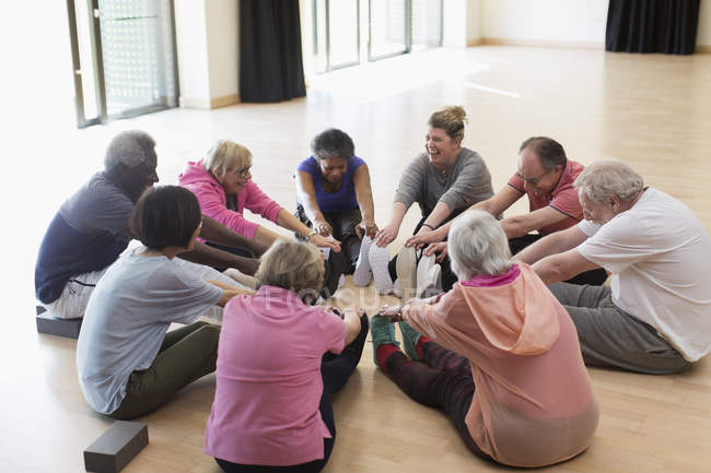 Active seniors exercising, stretching legs in circle — Stock Photo