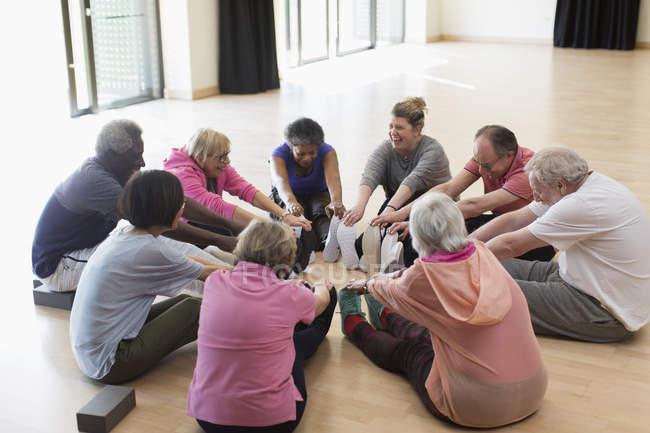 Активных пожилых людей, осуществляющих, растяжение ноги в круге — стоковое фото