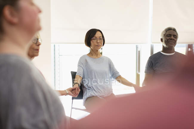 Serene active seniors holding hands and meditating in community center — Stock Photo
