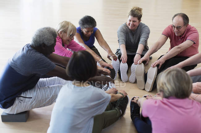 Smiling active seniors stretching legs in circle — Stock Photo