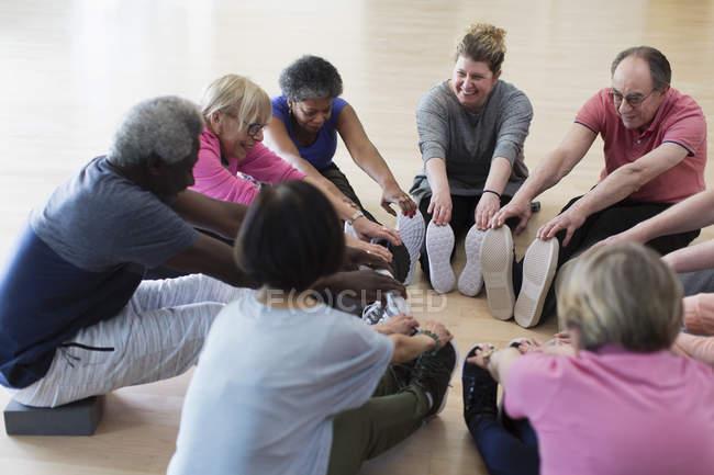 Adultos mayores activas sonrientes estirando las piernas en círculo - foto de stock