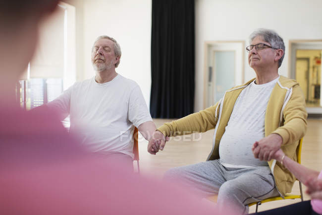 Serene active senior men holding hands, meditating in community center — Stock Photo
