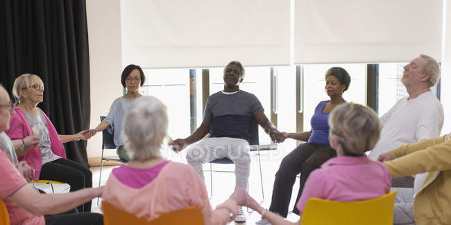 Serene active seniors holding hands, meditating in circle — Stock Photo