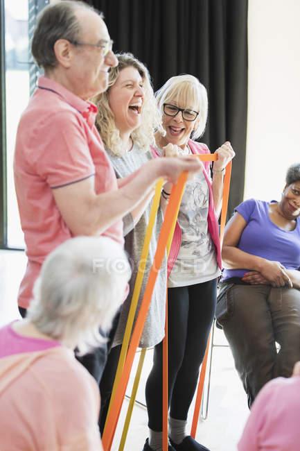 Lächelnd, aktive Senioren und Ausbilder stretching, Training mit Riemen — Stockfoto