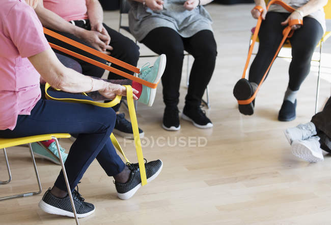 Active seniors stretching, exercising with straps — Stock Photo