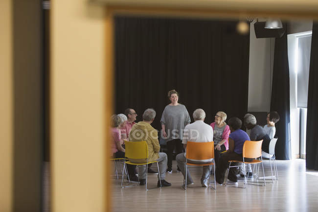 Woman leading seniors in group discussion in community center — Stock Photo