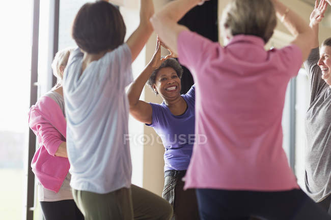 Smiling active senior woman exercising, practicing yoga tree pose — Stock Photo