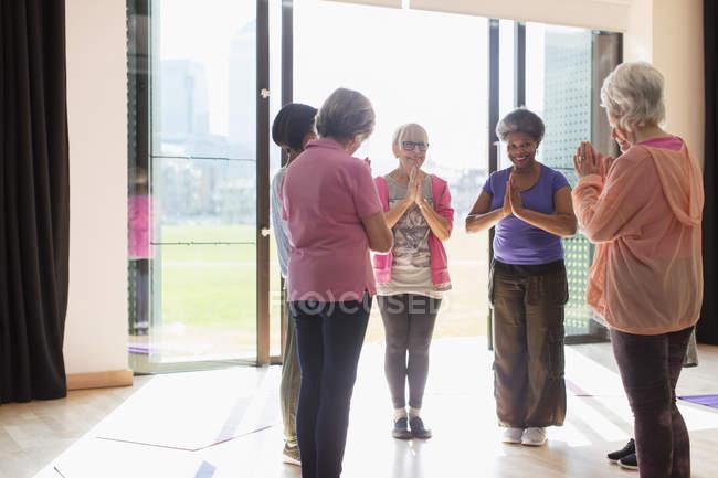 Sonriendo a senior femenino hacer ejercicio, practicar yoga en el estudio soleado - foto de stock