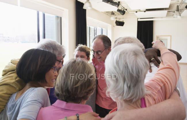 Active seniors hugging in circle huddle — Stock Photo