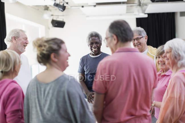 Active seniors talking in circle — Stock Photo