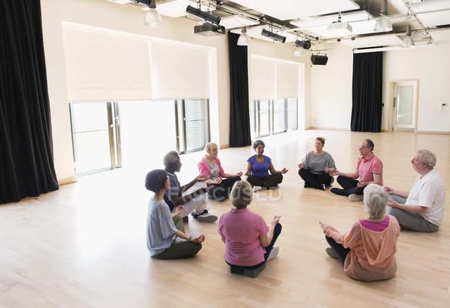 Serene active seniors meditating in circle — Stock Photo