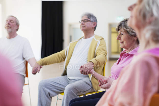 Serene active seniors holding hands, meditating — Stock Photo