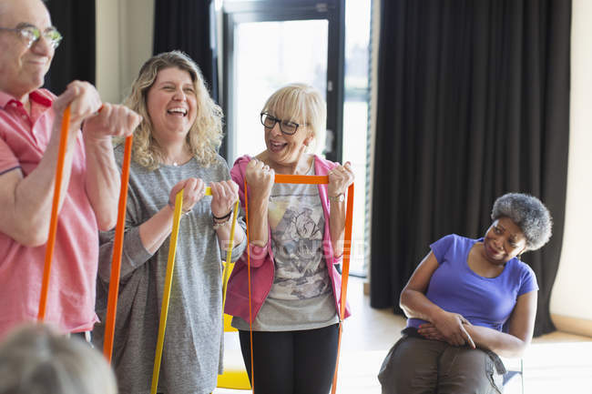 Happy instructor and active seniors exercising with straps — Stock Photo