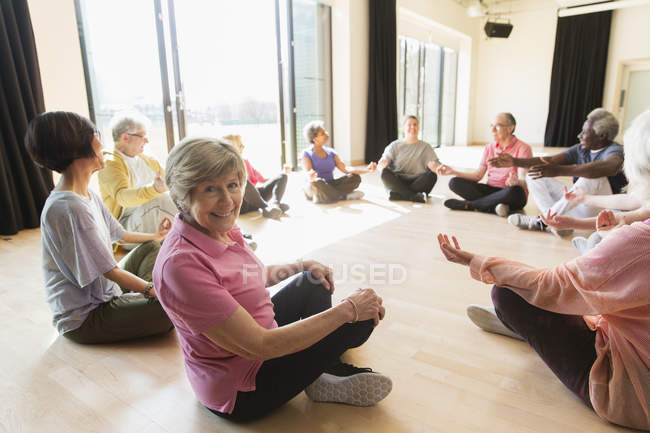 Portrait smiling active senior woman meditating in circle — Stock Photo