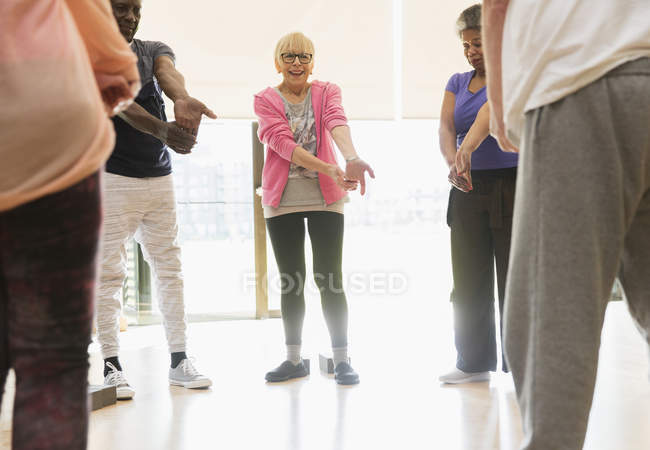 Active seniors stretching wrists in exercise class — Stock Photo