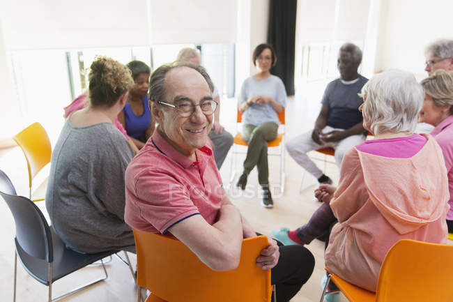 Portrait happy active senior man meeting with group in circle in community center — Stock Photo