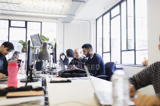 Businessmen working at laptop in open plan office — Stock Photo