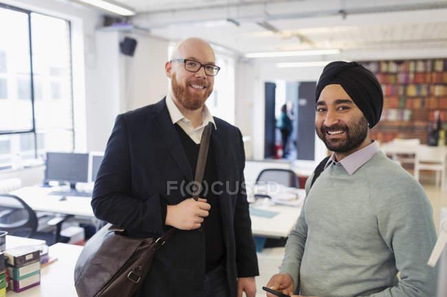 Retrato sonriente hombres de negocios en la oficina - foto de stock