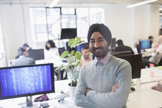 Портрет улыбается, уверенный индийский программист в тюрбане в офисе — стоковое фото