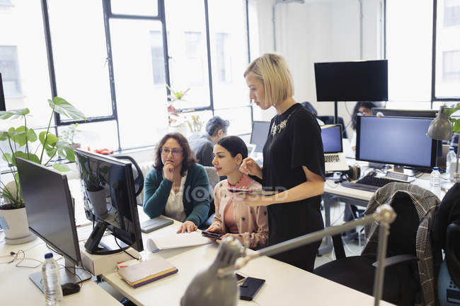 Businesswomen working at computer in open plan office — Stock Photo