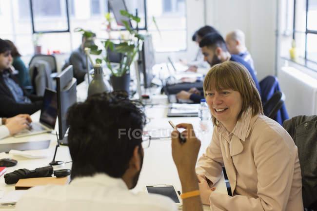 Empresaria sonriente escuchando empresario en oficina - foto de stock