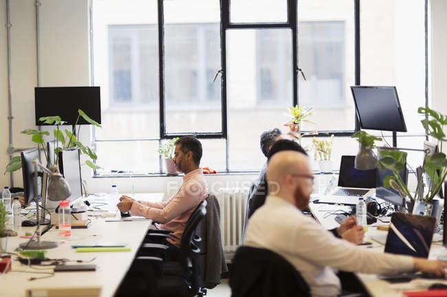 Geschäftsleute, die Arbeiten im Großraumbüro — Stockfoto