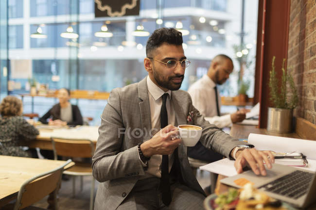Focused businessman drinking coffee and working at laptop in cafe — Stock Photo