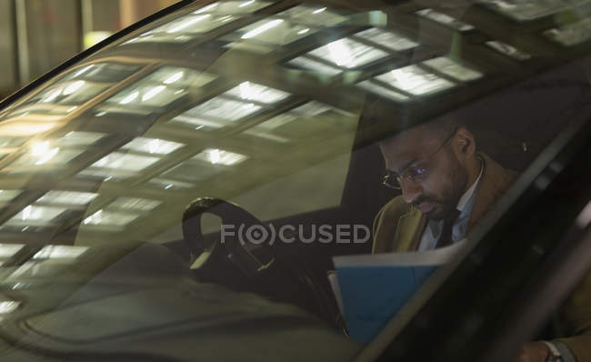 Businessman reviewing paperwork in car at night — Stock Photo