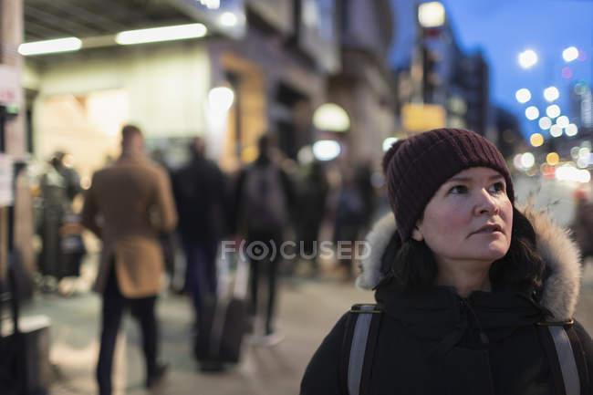 Mujer con ropa de abrigo en la acera urbana por la noche - foto de stock