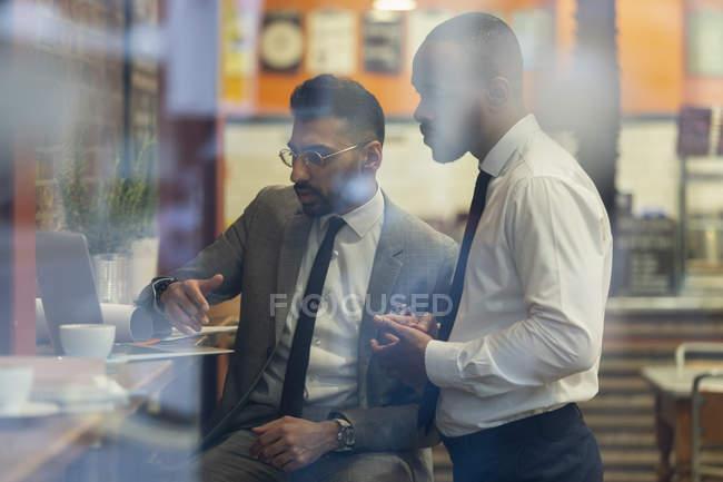 Hommes d'affaires travaillant à un ordinateur portable dans un café — Photo de stock