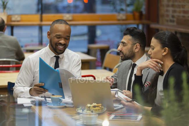 Geschäftsleute, die Schreibarbeit zu diskutieren, arbeiten im café — Stockfoto