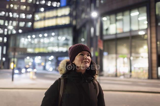 Mujer vestida de calidez caminando por la calle urbana por la noche - foto de stock