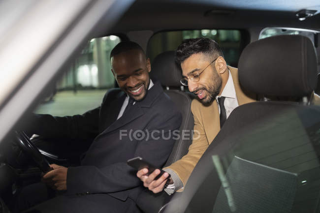 Uomo d'affari con smart phone utilizzando taxi crowdsourced — Foto stock