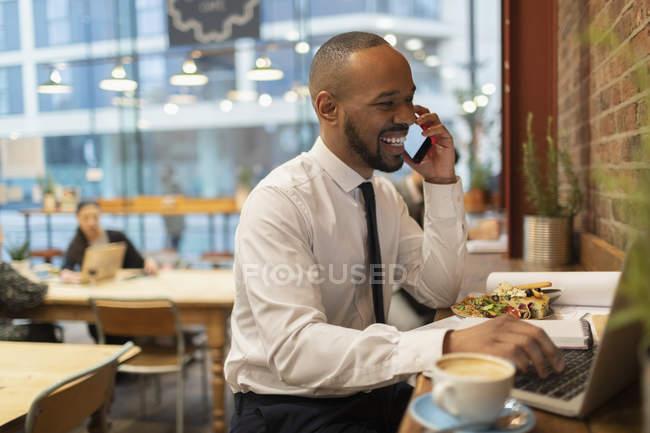 Uomo d'affari sorridente che parla su smart phone, lavora in un caffè — Foto stock