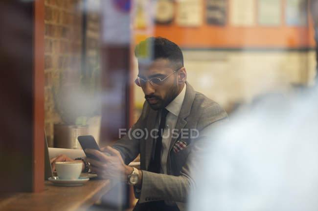 Uomo d'affari che utilizza lo smart phone, che lavora nel caffè — Foto stock