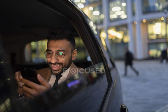 Uomo d'affari che utilizza lo smart phone in taxi crowdsourced di notte — Foto stock