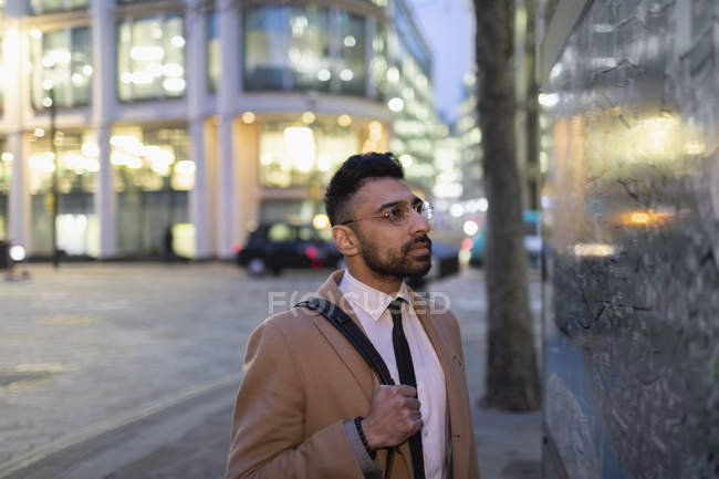 Businessman looking at city map on urban street at night — Stock Photo